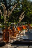 Fragment of table setting with dishes, wine glasses, bottles in the garden for dinner at sunset stock photos