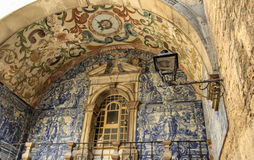 The fragment of 18th Century arch in Obidos, Portugal. The fragment of 18th Century arch covered in glazed tiles  and the old lamp. The picture was taken in Stock Photos
