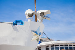 Fragment of a three-deck motor ship with searchlights. On a background of blue sky Stock Image
