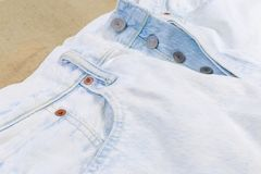 Fragment of the top of light colored artificially aged jeans. Upper part of the new light colored artificially aged jeans, fragment, close-up in selective focus stock photography