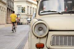 Fragment of Trabant car, bicyclist riding away stock photography