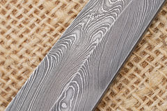 Fragment of the traditional handmade Finnish knife blade with the abstract wave pattern of damascus steel over an old sack backgro Stock Photography