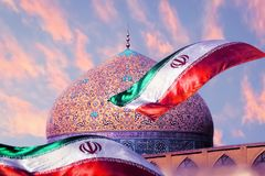 Fragment of traditional Iranian architecture and Iran`s national flag against the backdrop of sunset. royalty free stock photos