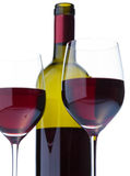 Fragment of two glasses of red wine, grape cluster. Fragment of two glasses of red wine and bottles in the background stock photography