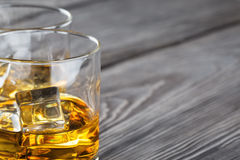 Fragment of two glasses of whiskey with ice Royalty Free Stock Photos
