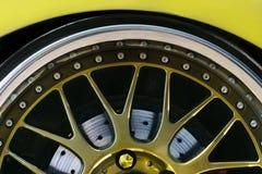 Fragment van de wielsportwagens, dun-profielbanden, remschijven, mooie die spokes in goud wordt geschilderd stock foto