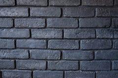 Fragment van een bakstenen muur De muur is geschilderde zwarte Achtergrond royalty-vrije stock afbeelding