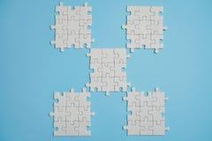 Fragment van een gevouwen witte puzzel en een stapel van uncombed raadselelementen tegen de achtergrond van een blauwe oppervlakt stock fotografie