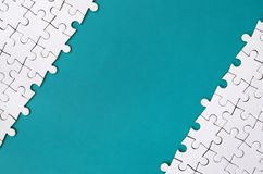 Fragment van een gevouwen witte puzzel op de achtergrond van een blauwe plastic oppervlakte Textuurfoto met exemplaarruimte voor  royalty-vrije stock afbeelding