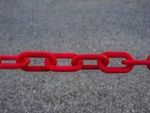 Fragment van een metaalketting van rode kleur op de achtergrond van grijs asfalt stock afbeelding