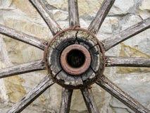 Fragment van een oude houten cartwheel tegen een muur van natuursteen stock foto's