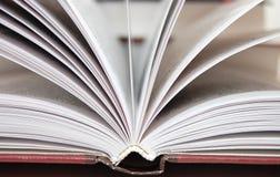 Fragment van het open boek tegen andere boeken Stock Afbeelding