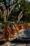 Fragment van lijst die met schotels, wijnglazen, flessen in de tuin voor diner bij zonsondergang plaatsen stock foto's