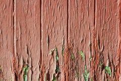 Fragment van oude door storm geteisterde rode deur, oppervlakte met doen barsten geweven verf Royalty-vrije Stock Afbeelding