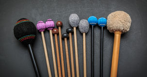 Fragment of view of  hand made  drum and percussion orchestra natural hickory wood sticks on dark grey Royalty Free Stock Photos