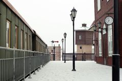 Vintage railway station in the winter landscape. Fragment of a vintage railway station with old wagons standing in rails in a winter landscape Royalty Free Stock Photo