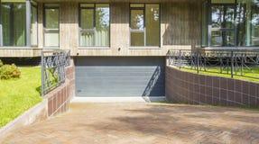 Fragment von neuen modernen Wohngebäudeäußeren Das Eingangstor zum Untertageparkplatz Lizenzfreie Stockfotografie