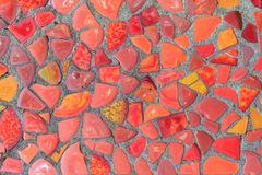 The fragment of the wall is decorated in red mosaic of different shades as a background or a backdrop Stock Photos