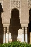 A fragment of the wall of the Moorish palace in Spanish Granada. Arch on white columns. Part of the architecture of the palace. Arab carving on the stone stock photography