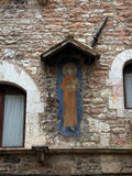 Fragment of a wall of an old building with a monk holding the word peace and good in Assisi Royalty Free Stock Photos