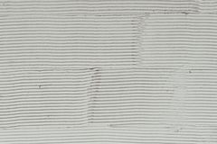 Fragment of a wall with scratches and cracks. White cement background with patterns stock images