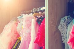 Fragment of the wardrobe with women`s dresses. Close-up, selective focus. Tinted photo. Fragment of the wardrobe with women`s dresses. Closeup, selective focus stock images