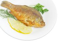 Fried crucian with lemon and potherb on white dish. Fragment of a white dish with fried crucian, slices of the lemon, twigs od the parsley and dill on a white Stock Photo