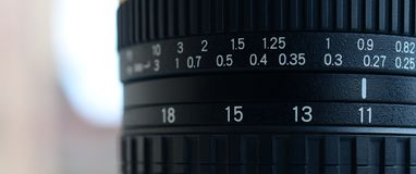 Fragment of a wide angle zoom lens for a modern SLR camera. The set of distance values is indicated by white numbers on the black Royalty Free Stock Photos