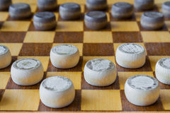 Wooden checkerboard with checkers spaced on table closeup Stock Photo