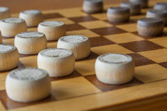 Wooden checkerboard with checkers spaced on table closeup Royalty Free Stock Photo