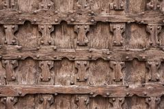 Fragment of a wooden door. A fragment of an ancient wooden tiled door in a medieval building Royalty Free Stock Photos