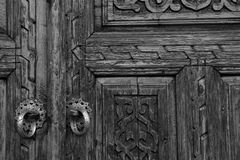 Fragment wooden door surface with carved patterns. Black and white view Royalty Free Stock Images