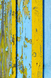 Fragment of wooden fence with cracked yellow and blue paint Stock Photos