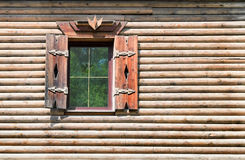A fragment of a wooden house with a window. Stock Image