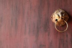 Fragment of the wooden painted door with ancient brass door knob. Chiangmai, Thailand Stock Photography
