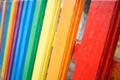 Fragment of a wooden rainbow fence stock photos