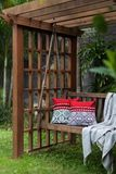 Fragment of wooden swing in the green garden with pillows and blanket. Fragment of wooden swing in the green garden with pillows and blanket Royalty Free Stock Images