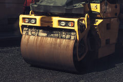 Fragment of yellow roller, urban road is under construction Stock Photos