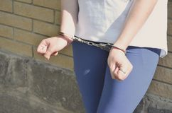 Fragment of a young criminal girl`s body with hands in handcuffs against a yellow brick wall background. The concept of detaining. An offender of a female stock images