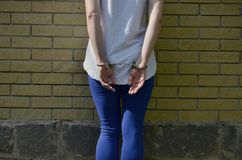 Fragment of a young criminal girl`s body with hands in handcuffs against a yellow brick wall background stock photo