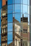 Historical buildings reflected in modern glass architecture. Fragmented and mixed parts of old houses reflect in curved glass wall of modern building Stock Images