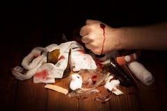 Fragmenterar brutet exponeringsglas, flaskor och den sårade handen som isoleras på svart Arkivfoton