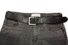 Fragmentet av den gråa höjdpunkten waisted jeans med det svarta läderbältet Arkivfoton