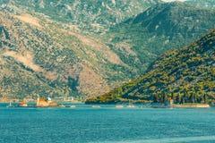 Fragmentet av den Kotor fjärden mot bakgrunden av bergen och öarna av Gospa med en liten kyrka och oskulden av vaggar Royaltyfri Foto