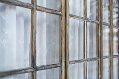 Fragmentet av en gammal farstubro med fönster stängde gardiner Arkivfoton