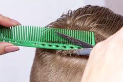 Fragmentet av huvudet för ` s för den unga mannen under klippning med frisörer scissors på suddig bakgrund av fönstret royaltyfria bilder