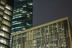 Fragmento abstrato do fundo da olá!-tecnologia de prédios de escritórios modernos da fachada do aço e do vidro com luzes nas  imagem de stock royalty free