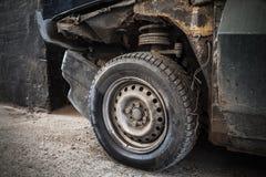 Fragmento aherrumbrado abandonado del coche con la rueda Imagen de archivo
