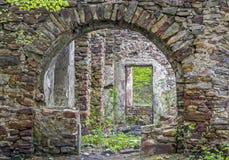 Fragmento das ruínas velhas de pedra cobertos de vegetação com as plantas Foto de Stock Royalty Free