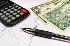 Fragmento de la calculadora electrónica con la pluma de bola y los dólares de EE. UU. de billetes de banco en el fondo del horari Imágenes de archivo libres de regalías